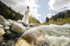 美丽的浴巾礼服的闺房性感的新娘 女孩时尚时髦与在北欧卡累利阿人的自然的花束 免版税库存照片