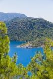美丽的海湾在有大海和杉树的爱琴海在山 免版税图库摄影