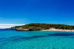 美丽的海滩用绿松石水拥挤了与游人在Cala Mondrago,马略卡 免版税库存图片
