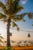 美丽的海滩用一个咖啡馆在萨努尔有在巴厘岛海岛上的地方传统小船棕榈树的在黎明 印度尼西亚 图库摄影