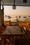 美丽的海滩用一个咖啡馆在萨努尔有地方传统小船的 巴厘岛印度尼西亚 黎明 免版税库存照片
