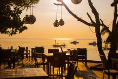 美丽的海滩用一个咖啡馆在萨努尔有地方传统小船的 巴厘岛 印度尼西亚 库存照片
