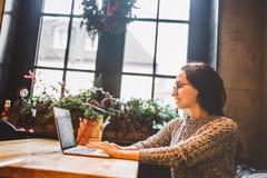 美丽的深色的女商人女商人在键盘使用一台膝上型计算机,拨号盘,印刷品发短信 在咖啡馆,坐在 库存图片