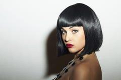 美丽的深色的女孩。健康黑发。突然移动理发。红色嘴唇。秀丽妇女 免版税库存照片