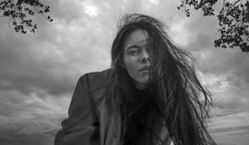 美丽的深色的女孩佩带的雨衣画象  免版税图库摄影
