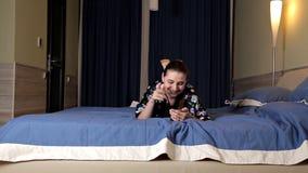 美丽的深色的女孩使用她的手机,当说谎在床上时 互联网约会 股票视频