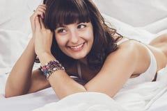美丽的深色的女孩在她的床上 图库摄影