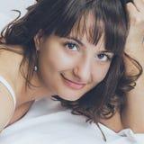 美丽的深色的女孩在她的床上 免版税库存图片