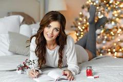 美丽的深色的女孩在床上在a说谎,微笑并且写 免版税库存照片
