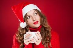 美丽的深色的女孩在拿着白色杯子的圣诞老人帽子 库存图片