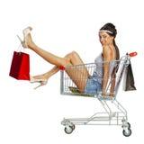年轻美丽的深色的女孩在空的购物车机智坐 免版税库存图片