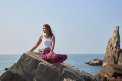 美丽的深色的女孩坐岩石反对天空,海在一件容易的夏天礼服没有寻找宽裤子 免版税库存图片