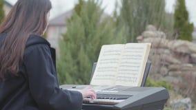 美丽的深色的女孩热情关于演奏合成器和唱坐在树下在后院户外 股票视频