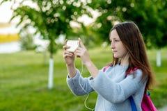 美丽的深色的女孩 夏天本质上 拿着一个智能手机 做照片 他听到他观看的音乐 免版税库存图片