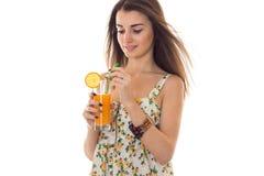 美丽的深色的女孩画象在sarafan的夏天与花卉样式喝在白色隔绝的橙色鸡尾酒 免版税库存照片