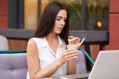 美丽的深色的女生在网上研究科学项目通过手提电脑,查寻,穿戴在典雅的白色 免版税库存图片