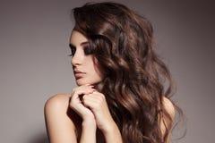 美丽的深色的妇女。卷曲长的头发。 免版税图库摄影
