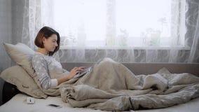 美丽的深色的妇女在家在与膝上型计算机的床上的piyamas穿戴了在卧室 有短小的女孩 股票视频