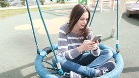 美丽的深色的妇女在空的作成蜘蛛网状摇摆摇摆, loking在手机的社会媒介 影视素材