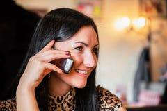 美丽的深色的妇女讲话由移动电话 库存照片