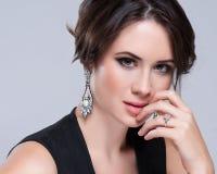 美丽的深色的妇女纵向黑色礼服的 装饰性的眼影膏 库存图片