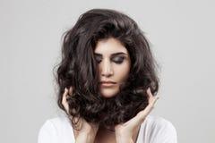 美丽的深色的妇女 卷曲长的头发 免版税库存照片