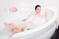 美丽的少妇洗泡末浴 免版税库存图片