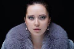 蓝蓝冬天皮大衣的美丽的妇女 库存图片