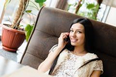 美丽的深色的少妇特写镜头画象谈话在电话有乐趣愉快的微笑的&看的照相机 免版税库存照片