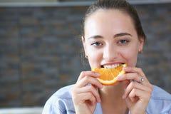 美丽的深色的微笑的妇女吃切的桔子 免版税库存照片