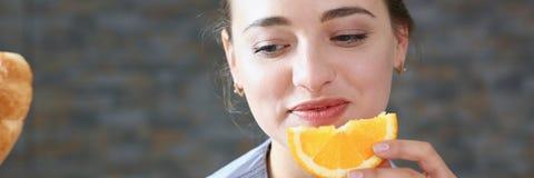 美丽的深色的微笑的妇女吃切的桔子 免版税图库摄影