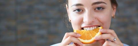 美丽的深色的微笑的妇女吃切的桔子 免版税库存图片