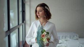美丽的深色的新娘在窗口附近拿着花花束 在头发的美丽的冠状头饰,专业构成 影视素材