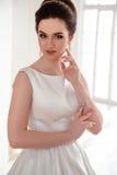 美丽的深色的新娘画象有典雅的穿长的豪华婚礼礼服的发型和构成的 免版税图库摄影