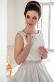 美丽的深色的新娘画象有典雅的穿长的豪华婚礼礼服的发型和构成的 免版税库存照片