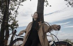美丽的深色的有自行车的女孩佩带的雨衣画象  免版税库存照片
