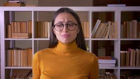 美丽的深色的老师画象玻璃的把头变成照相机在图书馆显示分歧和拒绝 股票视频