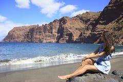 美丽的深色头发的女孩坐与山围拢的黑沙子的海滩 免版税库存图片