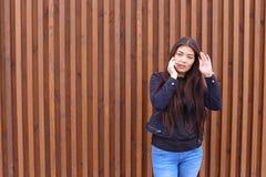 美丽的深色头发的妇女举行手中电话和谈话, smi 库存图片
