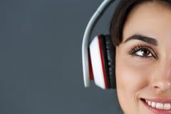 美丽的深色头发的微笑的妇女佩带的耳机 免版税库存照片