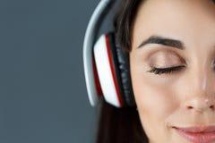 美丽的深色头发的微笑的妇女佩带的耳机 免版税库存图片