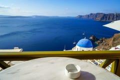 美丽的深蓝色爱琴海海洋全景海视图和蓝色教会屋顶从早餐咖啡店与白色大理石桌 库存照片