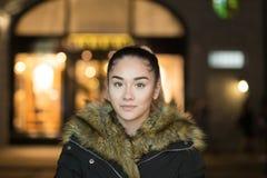 美丽的混合的族种女孩画象有毛皮大衣射击的在低灯在晚上 库存照片