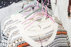 美丽的温暖的五颜六色的毛线衣在服装店里面的挂衣架垂悬 冬天秋天季节的美丽的衣裳 免版税库存照片