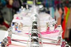 美丽的温暖的五颜六色的毛线衣在服装店里面的挂衣架垂悬 冬天秋天季节的美丽的衣裳 库存照片