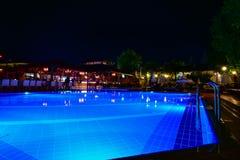 美丽的游泳池夜视图在热带手段的 库存照片
