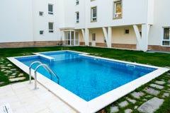 美丽的游泳池用在住宅复合体的水填装了 库存图片