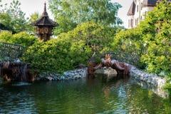 美丽的湖、锻铁篱芭和绿色庭院花和树 外面,公园 神仙的湖和人行桥surro 免版税库存照片