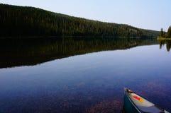 美丽的湖在有独木舟的森林 图库摄影
