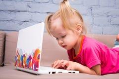 美丽的滑稽的白肤金发的女孩两年的孩子在长沙发说谎户内并且使用与co的白色便携式计算机技术 免版税库存图片